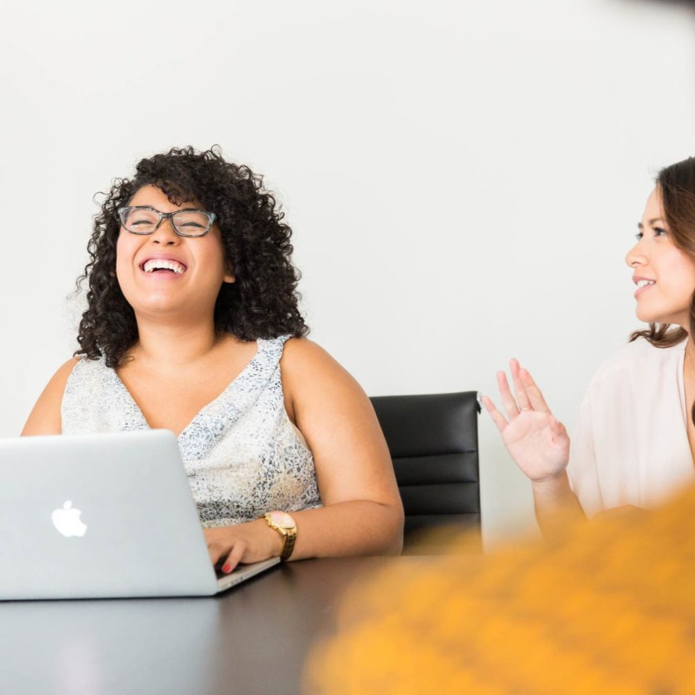 Two women--one with a laptop computer--sitting side-by-side at a conference table, laughing.